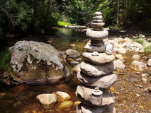 Rock Art On The River. A river with rocks placed as art with surrounding forest Royalty Free Stock Photos