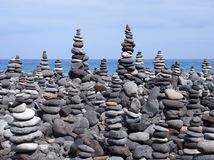 Rock art stacks and towers of grey stones and pebbles on a beach. Rock art stacked and towers of grey stones and pebbles on a beach with blue sky and blue sky Royalty Free Stock Image