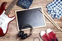 Rock background with music equipment, clothes and footwear on wo. Oden table with clean blackboard. Copy space for text Royalty Free Stock Photos