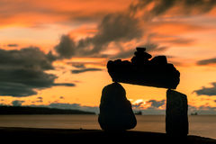 Rock balance on the beach with sunset clouds sky backgrounds Stock Photo