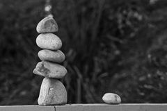 Rock Balance on the Fence in Black & White. Five stones are balanced on the post of a fence with blurred background. This stones are balanced on top of each Stock Photo