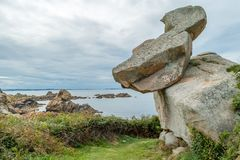 Rock balancing on another rock. Rocks balancing on another rock in Chemin des douaniers in Primel Brittany France Royalty Free Stock Photo