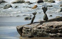 Rock balancing art on beach rocks in Laguna Beach, California. Image shows rock balancing art on beach rocks in Laguna Beach, California. An occassional wave stock photo