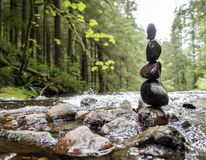 Rock balancing. Five wet rocks stacked and balancing on top of one another near a flowing river in the forest Royalty Free Stock Photography