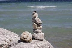 Rock balancing Stone stacking on coastline. Artfully arranged stones in sunlight along a coastline Stock Image
