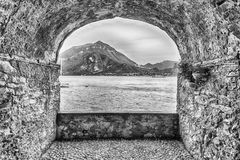 Rock balcony facing Lake Como in Varenna, Italy. Scenic rock arch balcony overlooking the Lake Como and the town of Menaggio in distance, Varenna, Italy Royalty Free Stock Images