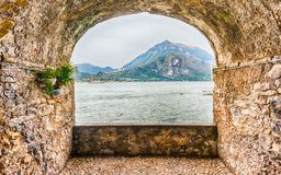 Rock balcony facing Lake Como in Varenna, Italy. Scenic rock arch balcony overlooking the Lake Como and the town of Menaggio in distance, Varenna, Italy Stock Photo
