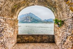 Rock balcony facing Lake Como in Varenna, Italy. Scenic rock arch balcony overlooking the Lake Como and the town of Menaggio in distance, Varenna, Italy Royalty Free Stock Image
