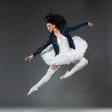 Rock and ballet. Jumping ballet dancer wearing leather jacket. Full length studio shot on gray background Royalty Free Stock Image