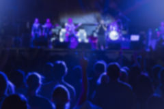 Rock band concert - defocused crowd and performers. Defocused crowd and band on the stage. Girl from the crowd with hand up. Blue light effect. Outdoor scene on Stock Photo