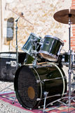 Rock band drum kit outdoors. Black drum kit with symbols and large speakers in back ground. Outdoor music Royalty Free Stock Photography