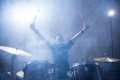 Rock band drummer on stage. Rock band drummer raising his arms on stage with light and smoke Stock Photo