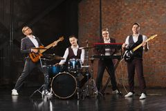 Rock band in an old industrial building. Music band and fashion. Handsome young men in suits playing rock and singing song Stock Photography