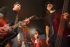 Rock band performing. Band playing on a stage. Guitarist, bassist and female drummer. Shot with strobes and slow shutter speed to create lighting atmosphere and Royalty Free Stock Photography