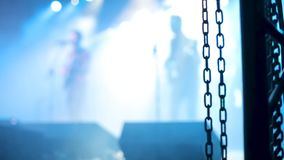 Rock band performing at a concert behind metal chains. Musicians singing and playing on a stage stock video