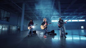 Rock band performing while shooting music video. Low angle camera quickly zooming in shooting rock band playing guitars with curly woman in leather jacket stock footage