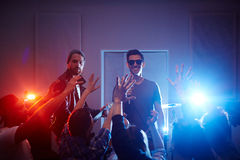 Rock Band Performing on Stage in Club. Handsome musicians performing on stage of urban club with crowd of cheering and dancing people partying, rising arms royalty free stock image