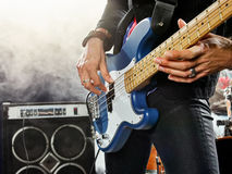 Rock band performs on stage. Bassist in the foreground. Stock Images
