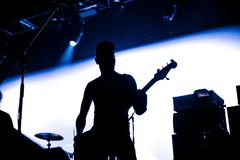 Rock band performs on stage. Guitarist plays solo. silhouette of guitar player in action on stage in front of concert crowd. Close. Rock band performs on stage stock images