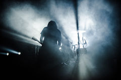 Rock band performs on stage. Guitarist plays solo. silhouette of guitar player in action on stage in front of concert crowd. Close-up. Dark background. Smoke Stock Image