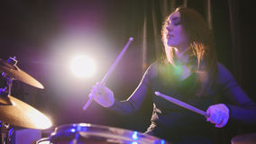 Rock band rehearsing in the garage - attractive girl percussion drummer perform music break down. Telephoto stock photography