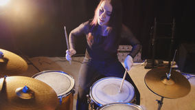 Rock band rehearsing in the garage - sensual dashing girl percussion drummer perform rock Stock Image