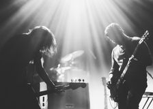 Rock band on a stage in a backlights. Rock band on a stage playing in a backlights, black and white silhouettes with the beautiful stage lights Royalty Free Stock Photos