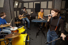 Rock band in studio. vocalist girl is singing. A rock band working in studio. vocalist girl is singing. focus on clothers of vocalist girl Royalty Free Stock Image