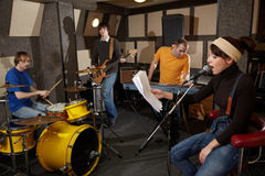 Rock band is working in studio. A rock band is working in studio. vocalist girl is singing with text of song in the her hand Stock Photography