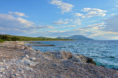 Adriatic sea beach at Losinj island, Croatia. Rock beach of the adriatic with mountains in the distance on a sunny summer day on Losinj island, Croatia Royalty Free Stock Photography