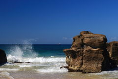 Rock on the beach. A big brown rock  beside the wave Stock Photography