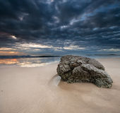 Rock on the beach with dramatic sky on square form Stock Images
