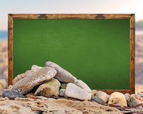 Rock on the beach with green school board picture frame and blur Stock Photos