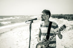Rock on the beach, the musician plays the guitar and sings into the microphone, the concept of leisure and creativity Stock Images
