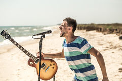 Rock on the beach, the musician plays the guitar and sings into the microphone, the concept of leisure and creativity Royalty Free Stock Images