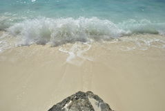 Rock on the beach. Rock pointing to the sea, with a strong wave on the seaside Royalty Free Stock Photos