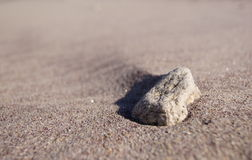 Rock in beach sand Royalty Free Stock Image