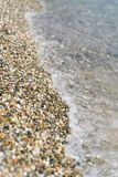 Water edge on white stone beach Royalty Free Stock Images