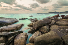 Rock beach at small island. Long explosure rock beach at small island and smoothe clouds Royalty Free Stock Photography