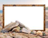 Rock on the beach with white board picture frame and blurred be Stock Photos