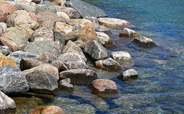 Rock bed along shoreline of clear blue lake waters Royalty Free Stock Image