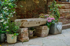 Rock bench near the wall among flowers Stock Photos
