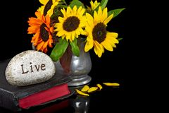 Rock on Bible with sunflower bouquet Stock Photo