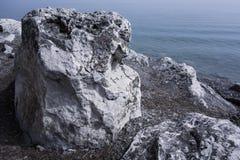 Rock or big boulder against the evening sea Stock Images