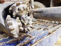 Rock bit sitting on the back of a rotary drill rig. Royalty Free Stock Image