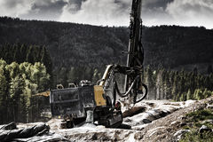Rock blasting drilling machinery. Giant drilling machine, drilling and excavating for rock blasting, dynamite civil-engineering and road-works Royalty Free Stock Images