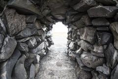 Rock boulder tunnel. Tunnel made from large rock boulders leading into a white backgroind Royalty Free Stock Images