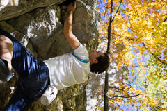 Rock Bouldering. Rock Climber bouldering hanging in the cliff, beautiful fall day in the mountains Stock Photo