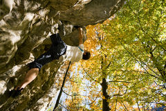 Rock Bouldering. Rock Climber bouldering hanging in the cliff, beautiful fall day in the mountains Stock Photos