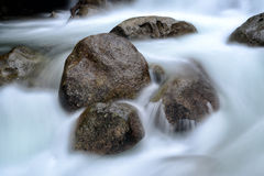 Rock boulders in flowing river waters. Creating a blurred motion effect royalty free stock images